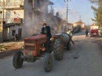 Köy muhtarı traktörüyle yolları dezenekte ediyor